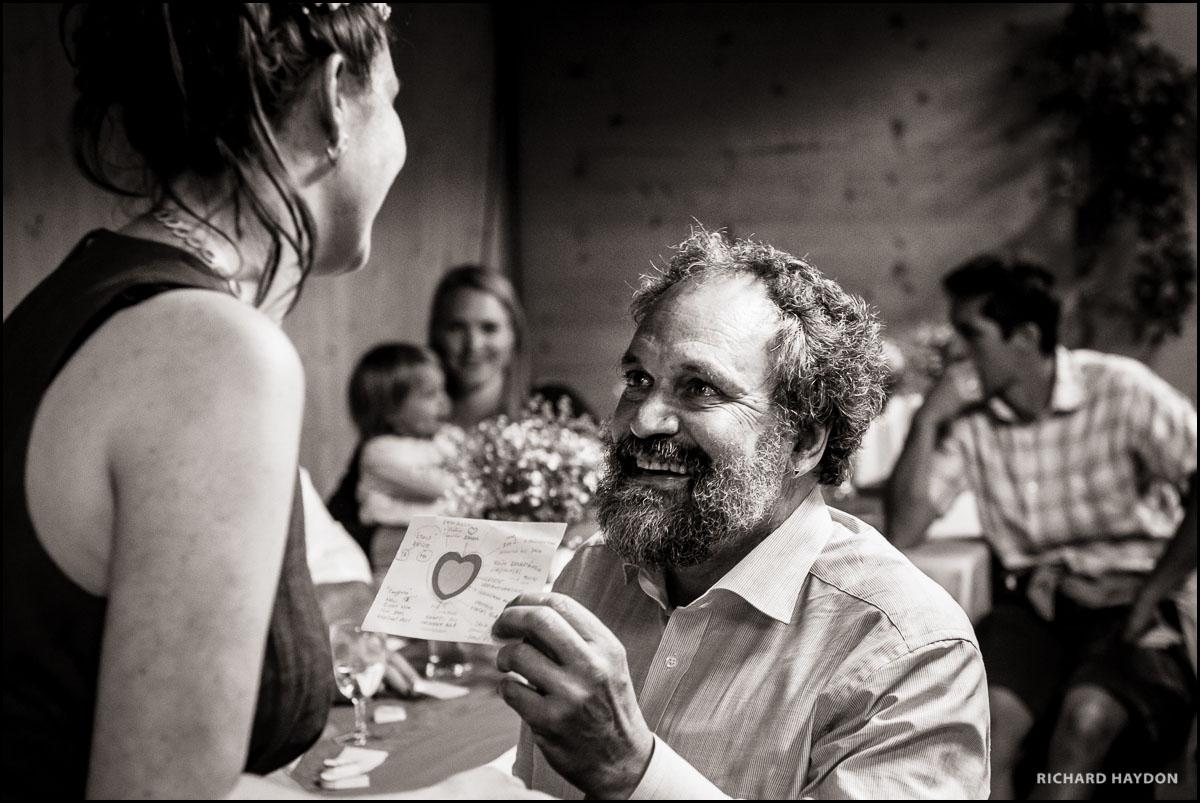 Vater hat Tränen in den Augen, als er seiner frisch verheirateten Tocher eine Karte übergibt.