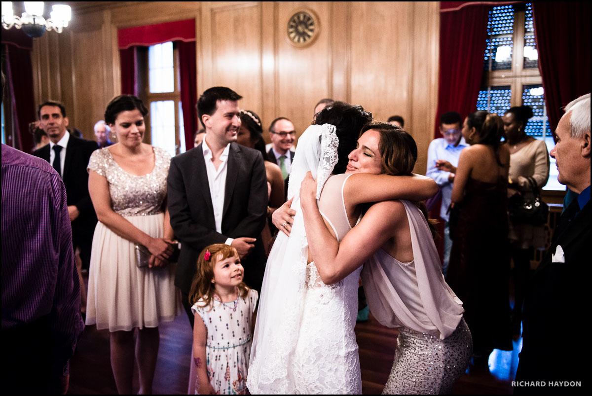 Umarmung der Braut während kleines Mädchen zuschaut - Hochzeitsfotograf Zürich