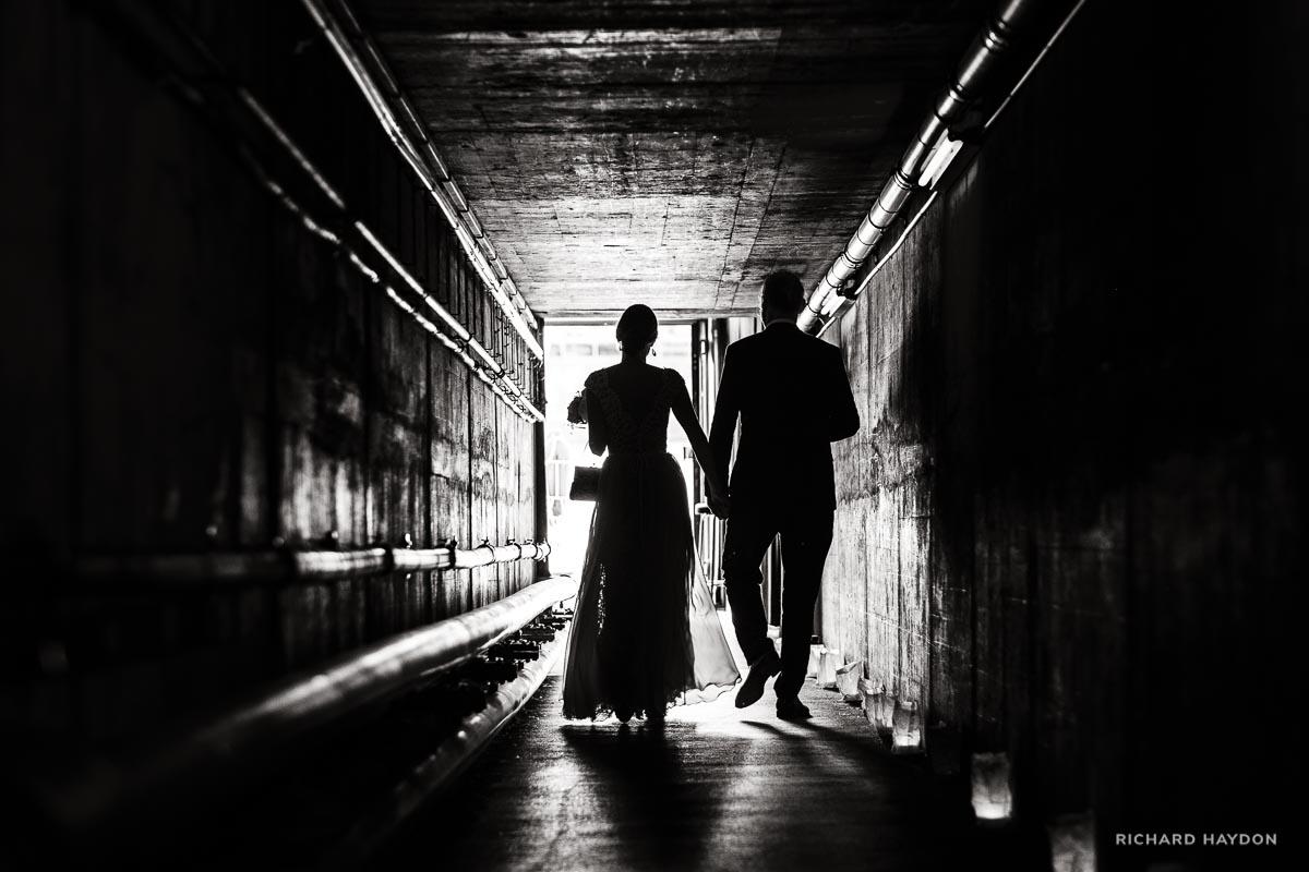 Braeutigam und Braut spazieren durch Tunnel