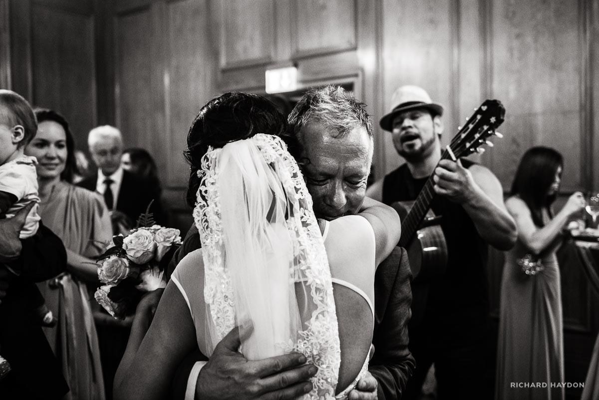 Mann hat Tränen in den Augen als er die Braut umarmt