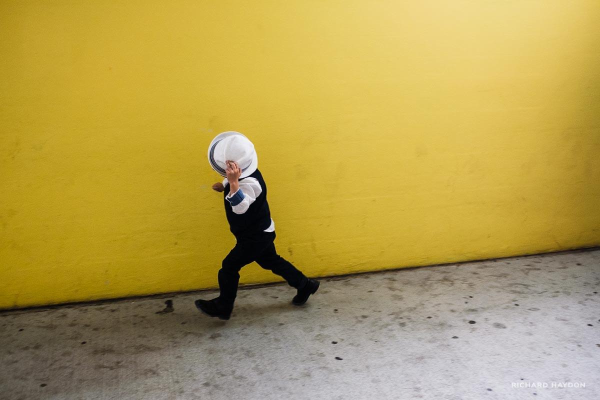 Ein kleiner Hochzeitsgast rennt mit Hut